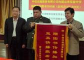 毛新宇少将向为韶山中学捐赠库存图书的中信出版社授锦旗